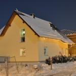 Weihnachtslichter am eingeschneiten Haus